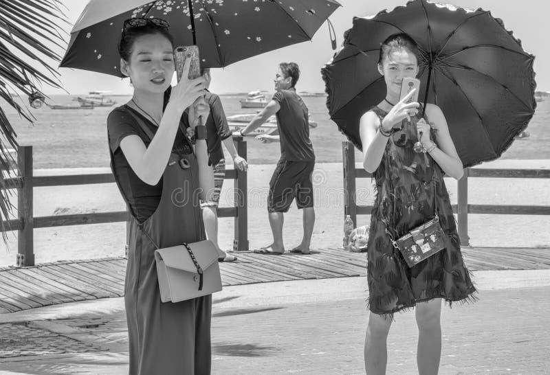 Deux jeunes et belles femmes chinoises tiraient les événements le dernier jour de Songkran, photo stock