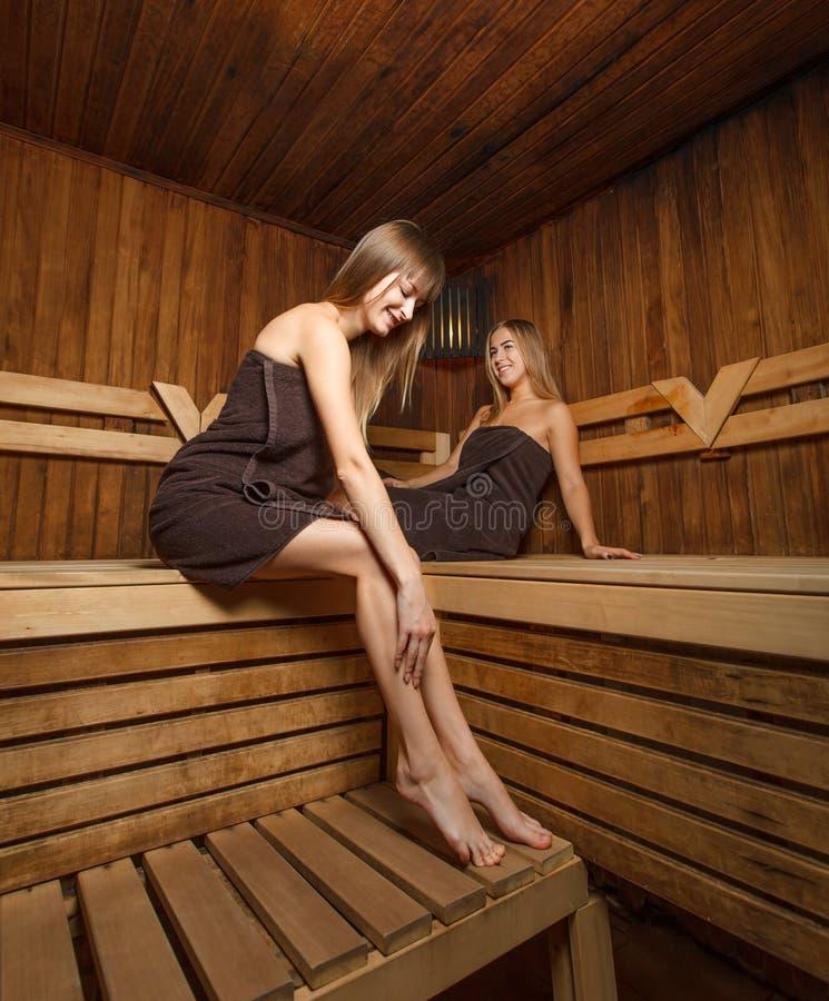 Deux jeunes et femelles heureuses dans le sauna images stock