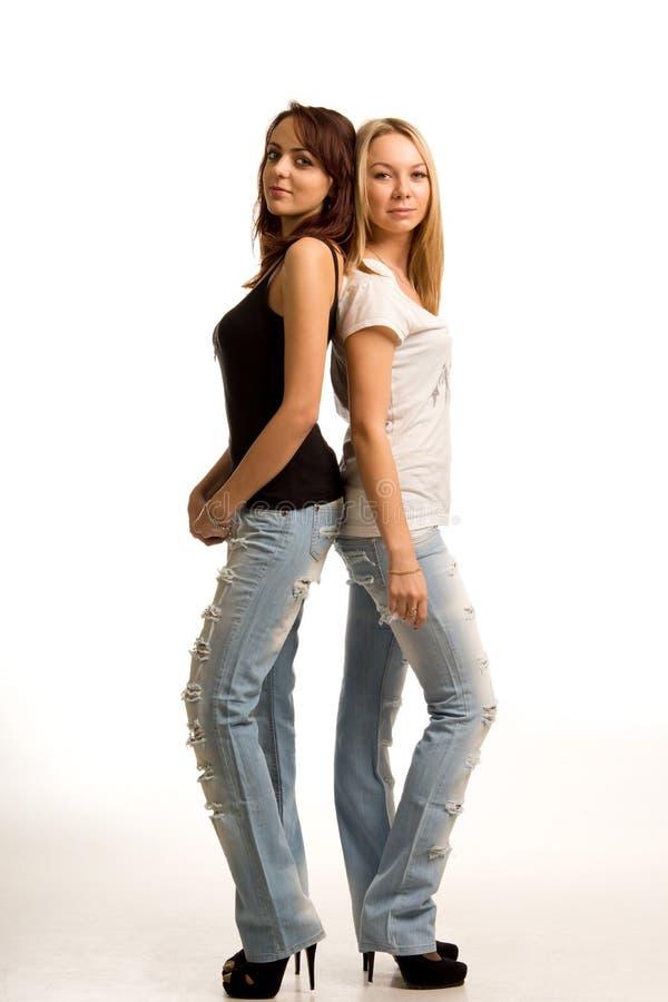Deux jeunes femmes à la mode restant de nouveau au dos photo libre de droits
