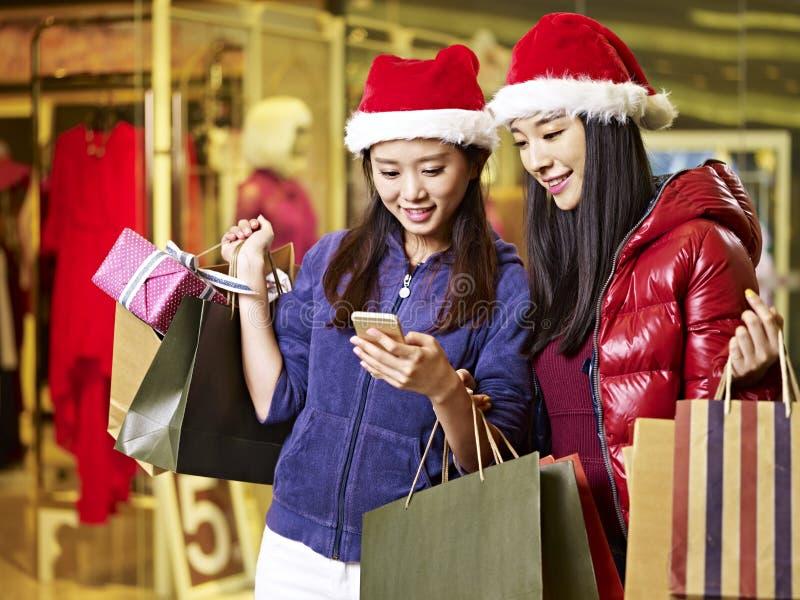 Deux jeunes femmes asiatiques faisant des emplettes pour Noël image stock