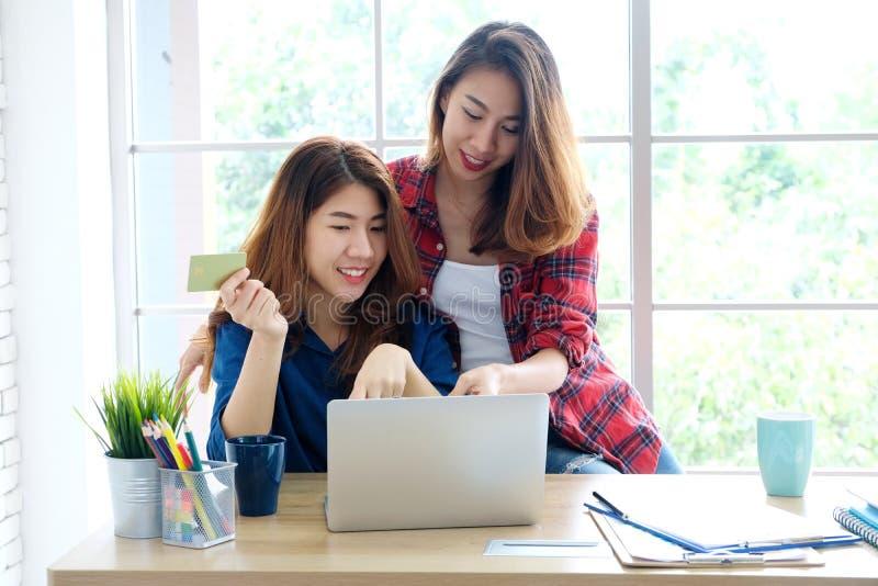 Deux jeunes femmes asiatiques tenant la carte de crédit et employant le compu d'ordinateur portable photographie stock libre de droits