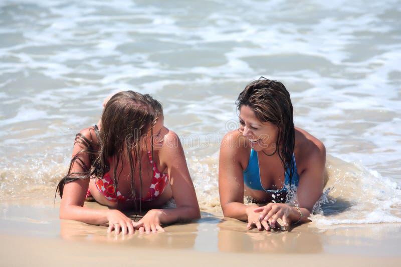 Deux jeunes femmes attirantes se trouvant sur une plage ensoleillée près de l'eau photographie stock libre de droits