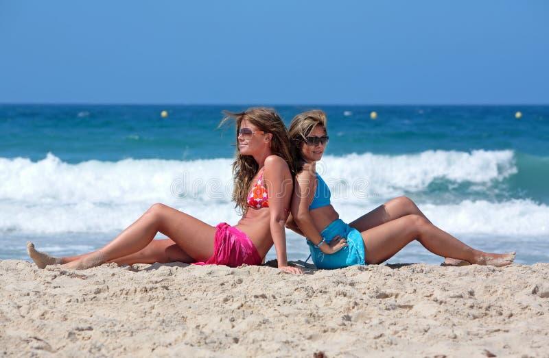 Deux jeunes femmes attirants refroidissant au soleil en vacances ou le VCA photos stock