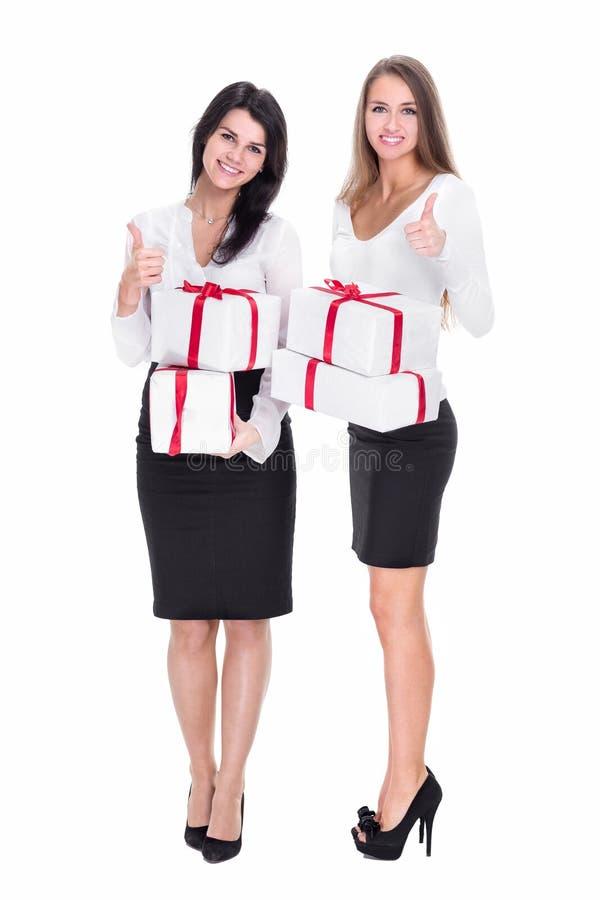 Deux jeunes femmes avec des bo?te-cadeau montrant des pouces  photos libres de droits