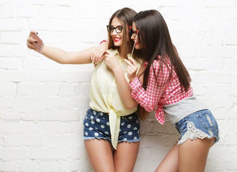 Deux jeunes femmes avec des verres de partie prenant le selfie photos libres de droits