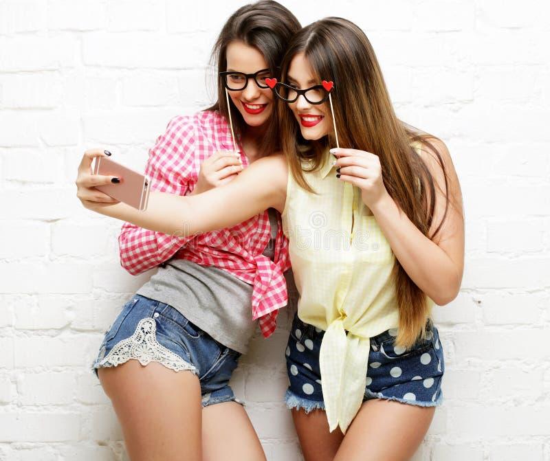 Deux jeunes femmes avec des verres de partie prenant le selfie image stock