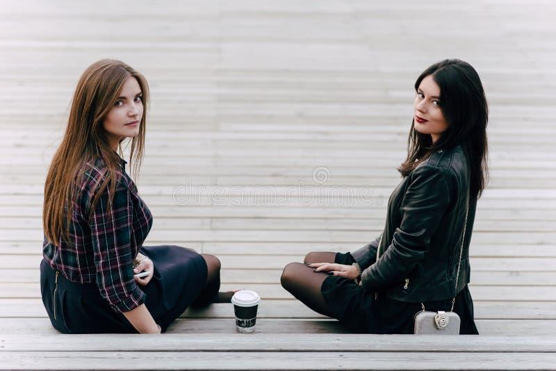 Deux jeunes femmes avec du charme posant tout en se reposant avec emportent le café sur les escaliers en bois à l'air frais, images libres de droits