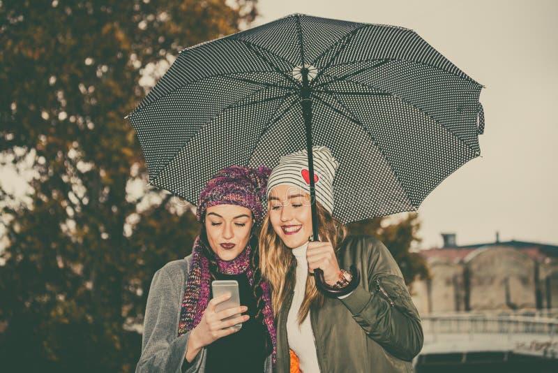 Deux jeunes femmes avec le parapluie et le téléphone portable d'utilisation dans le stre photo stock