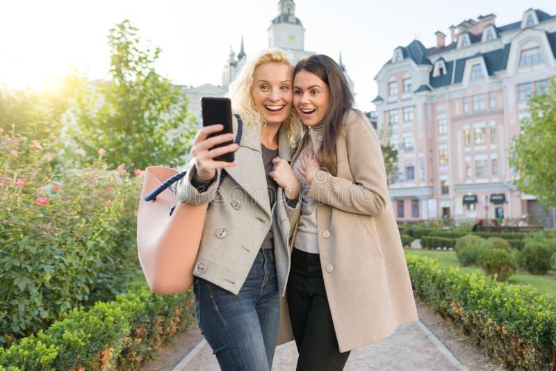 Deux jeunes femmes ayant l'amusement, regardant le smartphone riant, jour ensoleillé d'automne, fond de ville, heure d'or photos libres de droits