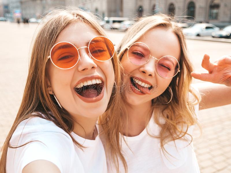 Deux jeunes femmes blondes hipster souriantes en t-shirt blanc en été images stock