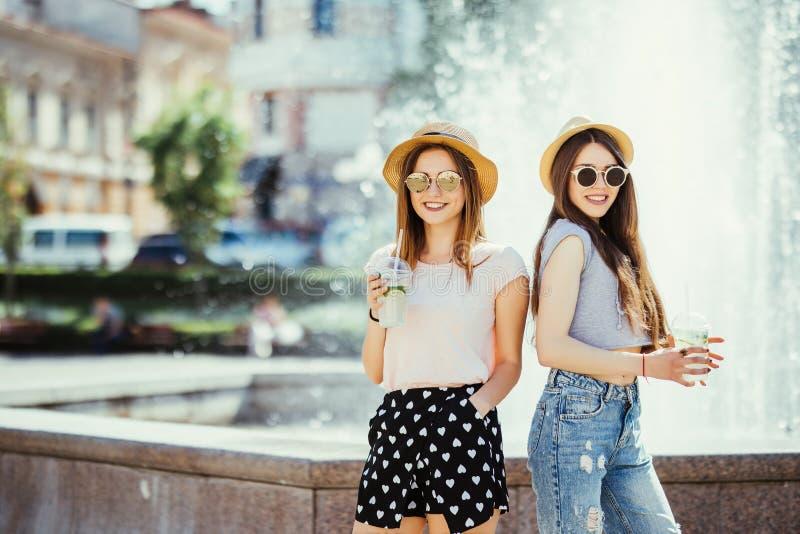 Deux jeunes femmes buvant les cocktails colorés des bouteilles dans la rue Dehors portrait de mode de vie images libres de droits