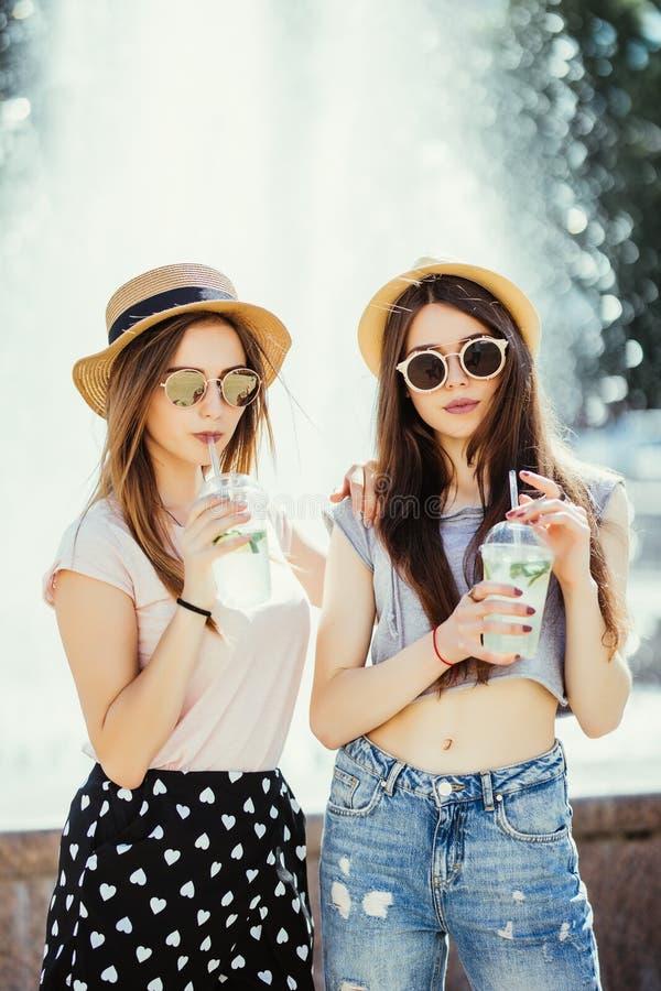 Deux jeunes femmes buvant les cocktails colorés des bouteilles dans la rue Dehors portrait de mode de vie photos libres de droits