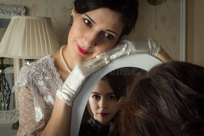 Deux jeunes femmes dans des robes de cru regardent l'un l'autre par un miroir, une réflexion de l'amour A ajouté un petit grain,  photographie stock libre de droits
