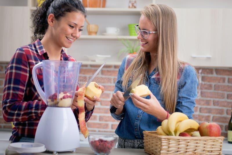Deux jeunes femmes dans la cuisine, le régime et le concept sain de la vie photos libres de droits