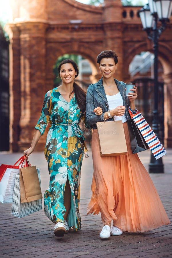 Deux jeunes femmes de mode avec des paniers dans la ville image stock