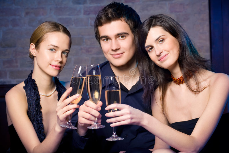 Deux jeunes femmes doux attirants et homme avec des glaces de champagne image libre de droits