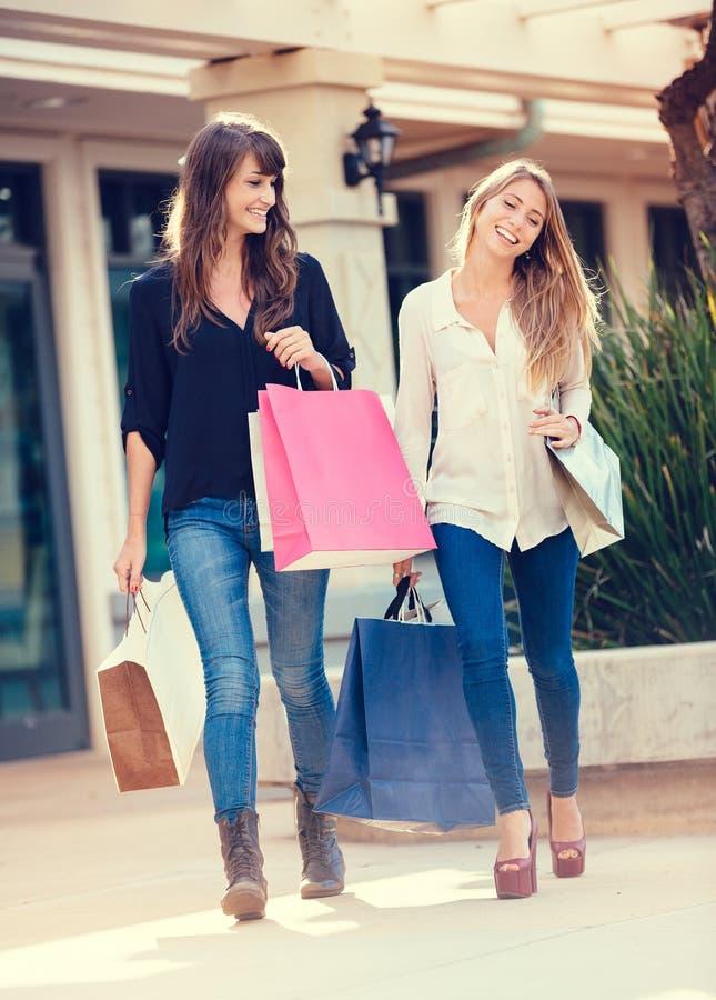 Deux jeunes femmes faisant des emplettes au mail photo libre de droits
