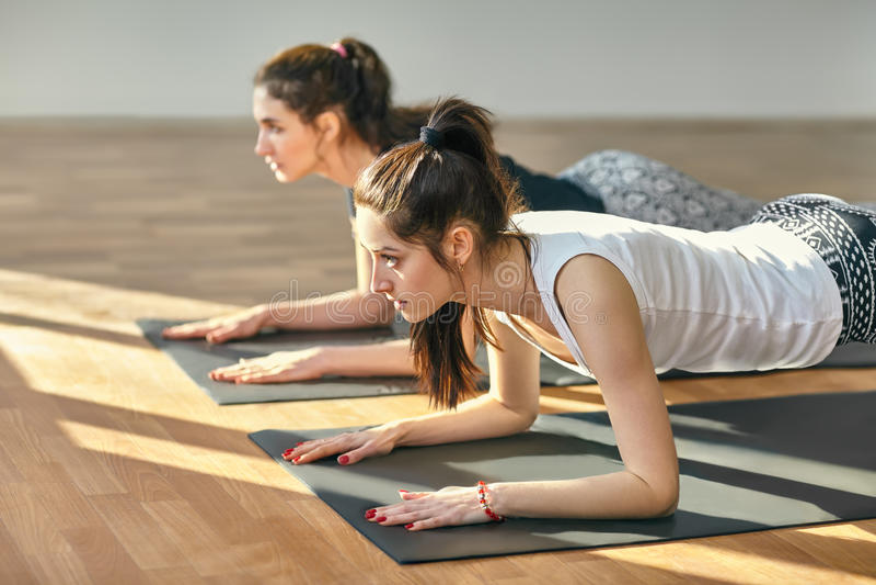 Deux jeunes femmes faisant pose de planche d'asana de yoga la basse image stock