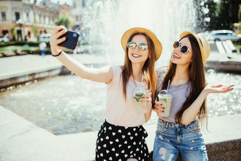 Deux jeunes femmes gaies posent contre la fontaine avec le smoothie, font le selfie au téléphone portable moderne ou parlent en l photographie stock