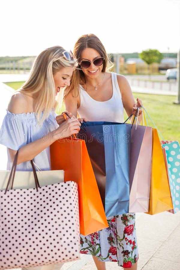 Deux jeunes femmes heureuses de sourire retournant des achats photographie stock