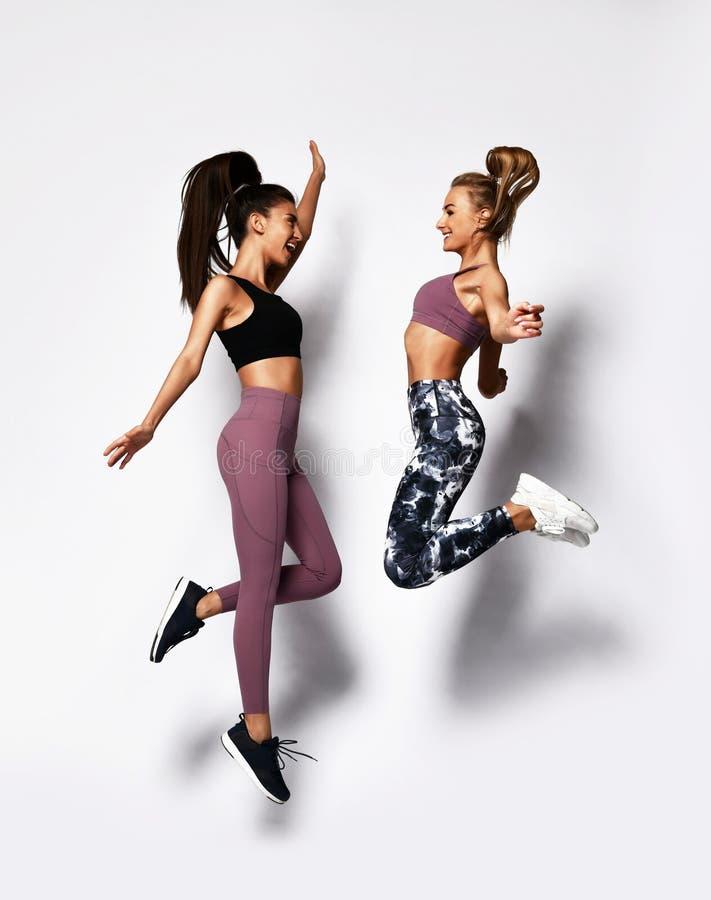 Deux jeunes femmes insouciantes heureuses de sport sautant la danse riant sur le blanc photo stock