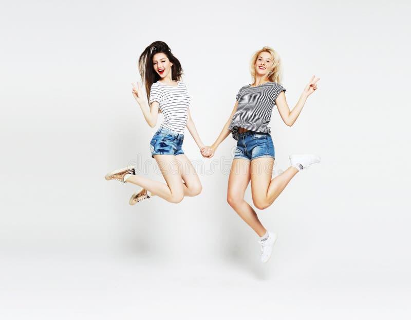 Deux jeunes femmes insouciantes heureuses sautant par-dessus le fond blanc photographie stock