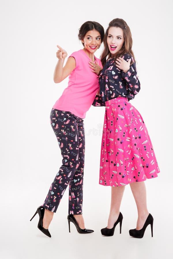 Deux jeunes femmes mignonnes de sourire parlant et se dirigeant loin photos libres de droits