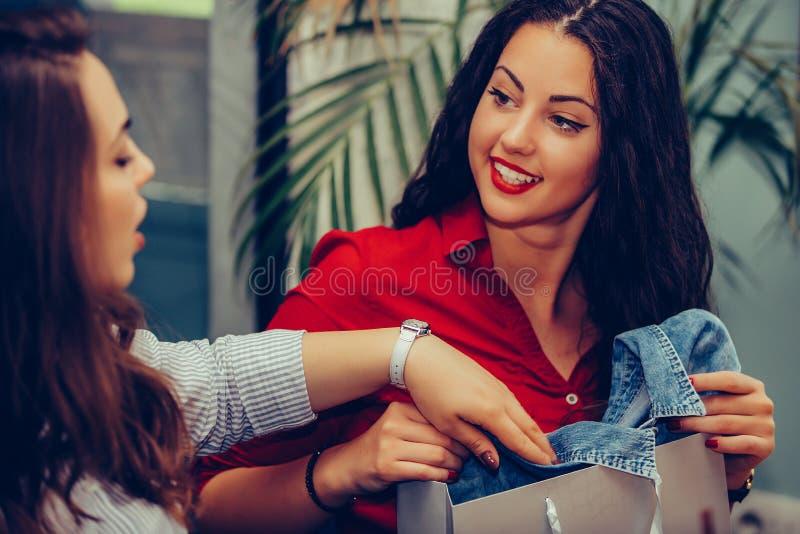 Deux jeunes femmes partageant leurs nouveaux achats les uns avec les autres image stock