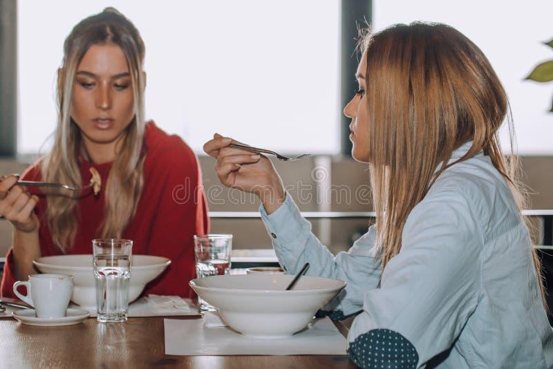 Deux jeunes femmes prenant le déjeuner ensemble dans un restaurant photographie stock