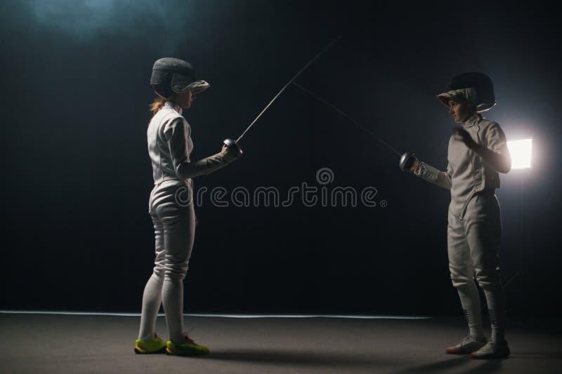 Deux jeunes femmes qui s'entraînent dans un duel d'escrime au studio fumé - se saluent et commencent le duel photographie stock libre de droits