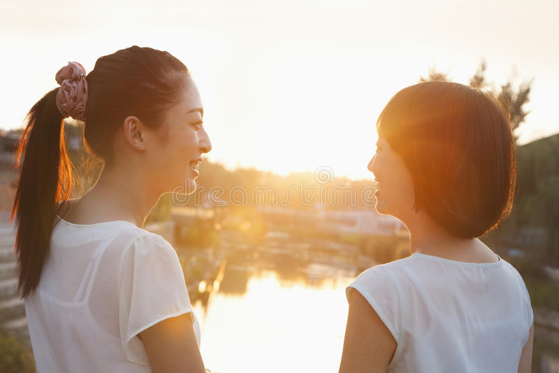 Deux jeunes femmes regardant le coucher du soleil image libre de droits