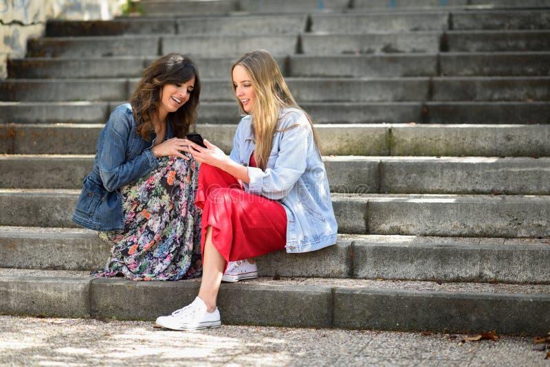 Deux jeunes femmes regardant un téléphone intelligent dehors photos stock