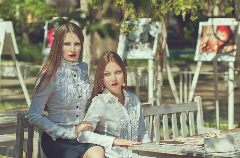 Deux jeunes femmes sérieuses avec de longs cheveux et lèvres rouges photos libres de droits