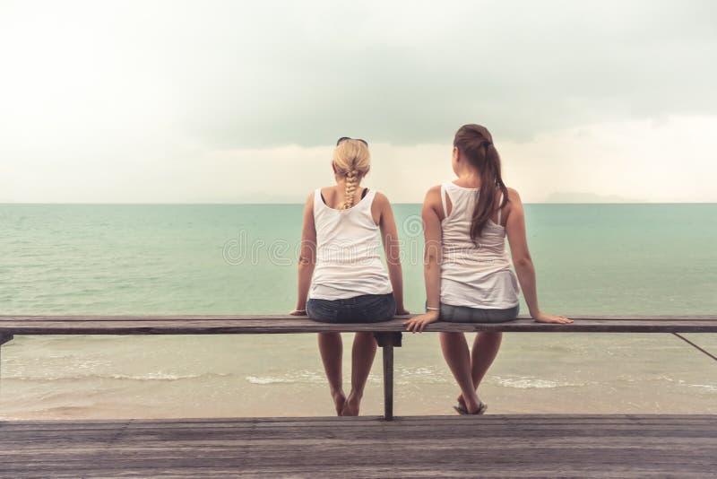 Deux jeunes femmes s'asseyant ensemble et examinant la distance sur la plage Concept pour l'unité photographie stock libre de droits