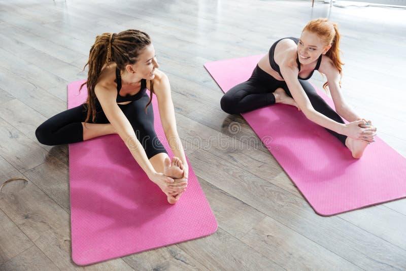 Deux jeunes femmes s'asseyant et s'étirant au centre de yoga image stock