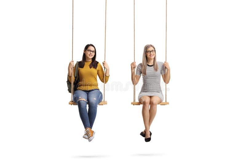 Deux jeunes femmes s'asseyant sur une oscillation et souriant à la caméra images libres de droits
