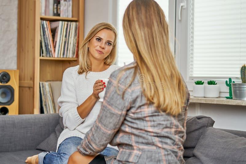 Deux jeunes femmes s'asseyent sur un divan et parler et rire photos stock