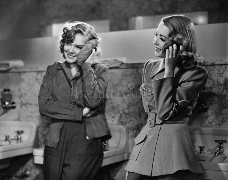 Deux jeunes femmes se penchant contre un évier de salle de bains et appliquant des vessies de glace dessus à leurs visages (toute photo stock