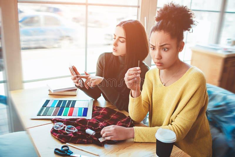 Deux jeunes femmes se tenant ensemble et travaillant pour le même projet de mode Aucun indice comment faire ceci Remy les vêtemen photos stock
