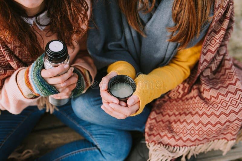 Deux jeunes femmes servent un thermos et une tasse chaude photo stock