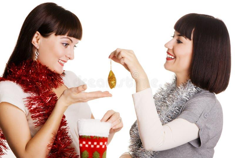 Deux jeunes femmes sortant leur cadeau de Noël photographie stock libre de droits