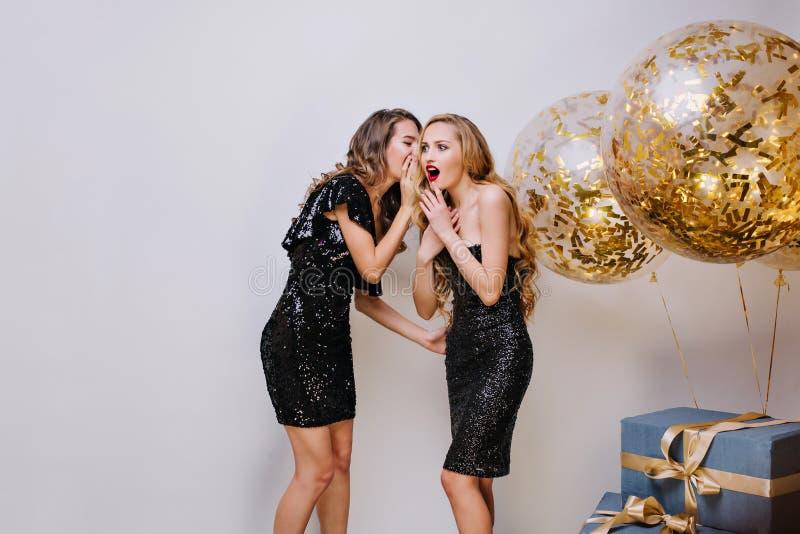 Deux jeunes femmes stupéfiantes dans des robes élégantes noires ayant l'amusement sur le fond bleu Fille de bavardage, chuchotant photo libre de droits