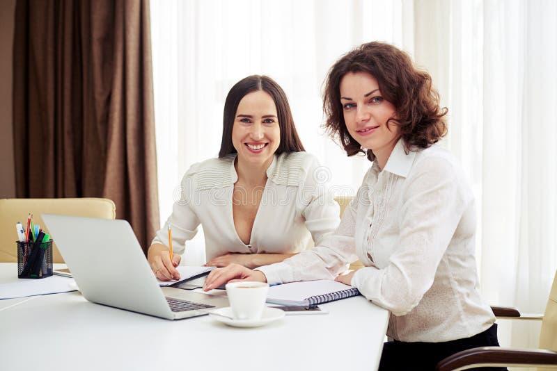Deux jeunes femmes teamworking avec des instruments à la table image stock