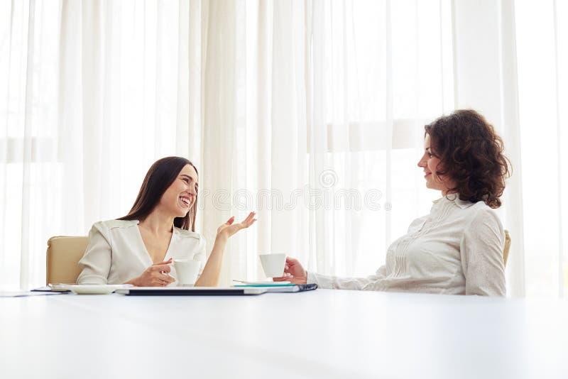 Deux jeunes femmes travaillent à l'équipe et au café potable image stock