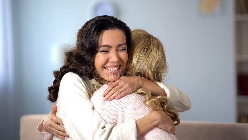 Deux jeunes femmes ?treignant et souriant sinc?rement, v?ritable vieille amiti?, ? l'int?rieur photos libres de droits