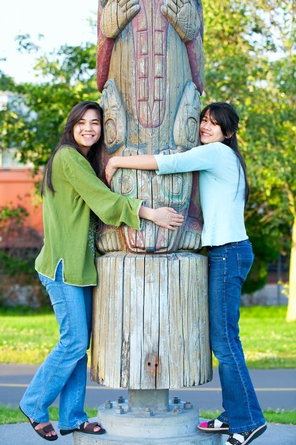 Deux jeunes, fille de l'adolescence biracial en parc étreignant un poteau de totem sur le su photographie stock libre de droits