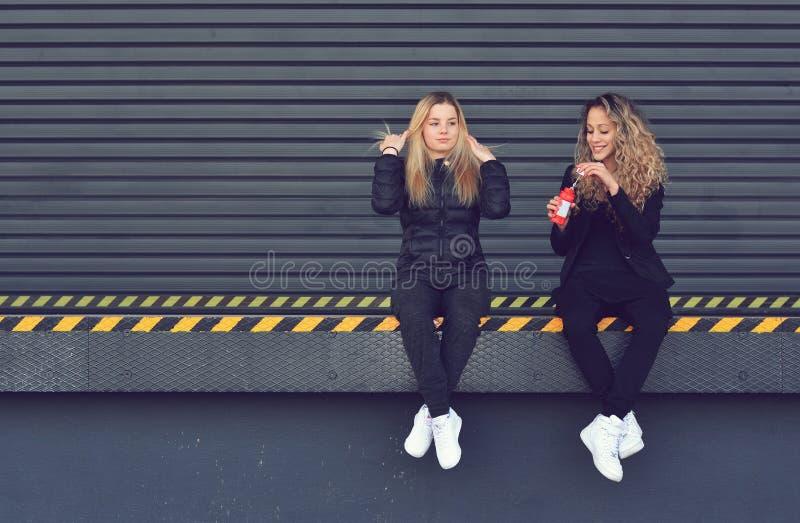 Deux jeunes filles élégantes reposant et soufflant des bulles images stock