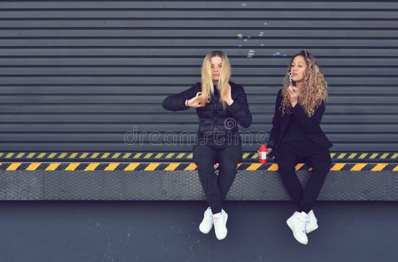 Deux jeunes filles élégantes reposant et soufflant des bulles images libres de droits