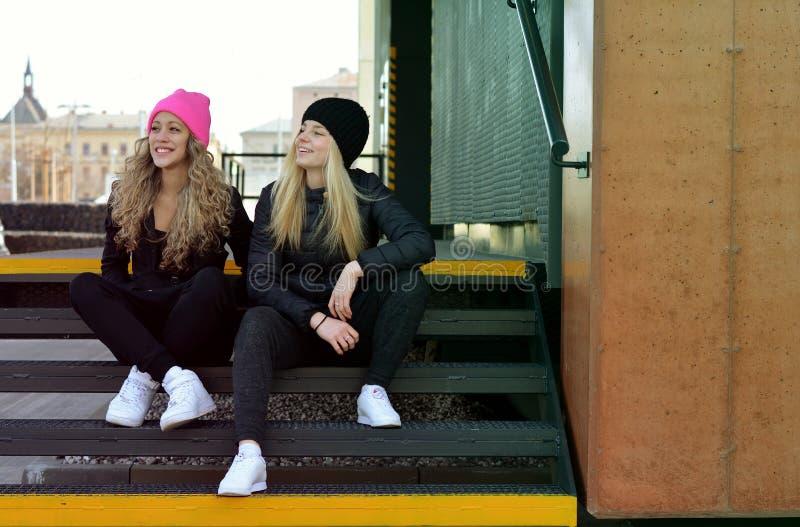 Deux jeunes filles élégantes s'asseyant sur des escaliers images stock