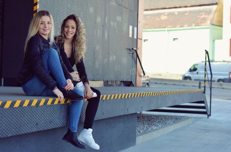 Deux jeunes filles élégantes s'asseyant sur la rue photos libres de droits